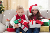 Festive siblings surrounded by gifts — Stock fotografie