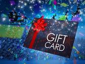 Santa flying behind gift card — Stockfoto