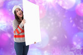 Composite image of excited brunette in santa hat showing white p — Stock Photo