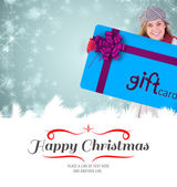 Blonde in winter clothes showing card — Stock Photo