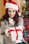 Festive brunette showing gift at christmas — Стоковое фото