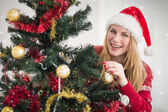 Woman hanging christmas decorations on tree — Stock Photo