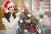 Smiling brunette holding a bauble at christmas — Stock Photo