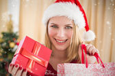 Festive blonde showing gift — Stock Photo