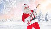 Smiling santa playing electric guitar — Stock Photo