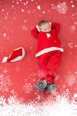 Boy napping in santa costume — Stock Photo