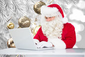 Composite image of santa using laptop — Foto de Stock