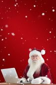 Santa pays with credit card on laptop — Photo
