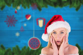 Composite image of festive blonde looking surprised with hands o — Stock Photo