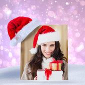 Festive brunette in santa hat holding gifts — Stock fotografie