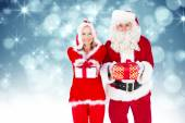 Santa and mrs claus smiling at camera offerin — Stock Photo