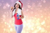Composite image of festive fit brunette holding bottle and apple — Foto de Stock