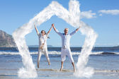 Happy couple jumping up barefoot on the beach — Stock Photo