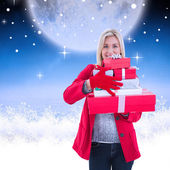 Festive blonde holding many gifts — Stock Photo