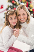 Festive mother and daughter beside christmas tree — Stock Photo