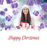 Festive brunette holding gifts — Stockfoto