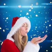 Pretty santa girl blowing over hand — Stockfoto