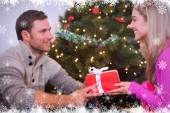 Composite image of sitting couple giving each other presents — Stock Photo
