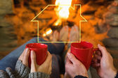 Hands with red coffee cups in front of lit fi — Stock Photo