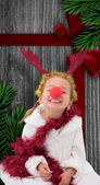Composite image of cute little girl wearing red nose and tinsel — ストック写真