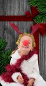 Composite image of cute little girl wearing red nose and tinsel — Zdjęcie stockowe