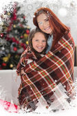 Festive mother and daughter wrapped in blanket — Stock Photo