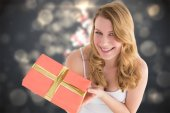 Composite image of cute blonde holding a gift — Stock Photo