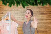 Composite image of smiling woman giving thumbs up — Stock Photo