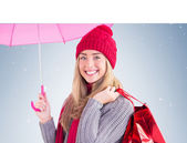 Blonde holding umbrella and bags — Stock Photo