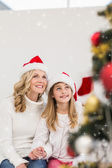 Festive mother and daughter smiling at tree — Stock Photo