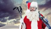Happy santa posing with ski and ski poles — Zdjęcie stockowe