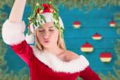 Composite image of festive cute blonde holding mistletoe  — Stock Photo