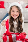 Festive little girl smiling at camera with gifts — Foto Stock