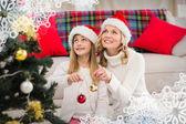 Mutter und tochter schmücken weihnachtsbaum — Stockfoto