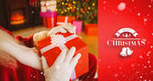 Santa claus holding red gift — Stok fotoğraf