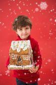 Festive boy holding gingerbread house — Stock Photo