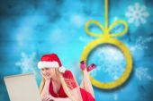 Composite image of festive blonde using a laptop — Stock Photo