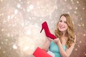 Composite image of elegant brunette admiring a shoe — Stock Photo