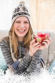 Happy blonde in winter hat sitting — Stockfoto