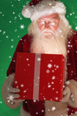 Father christmas opening gift — Stock Photo