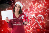Composite image of brunette holding gift and sale sign  — Stock Photo