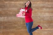 Composite image of happy brunette in winter clothes holding pres — Stock Photo