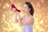 Composite image of elegant brunette kissing a shoe  — Стоковое фото