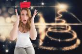 Woman balancing christmas gift on her head — Stock Photo