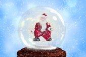 Santa doing yoga in snow globe — Stock Photo