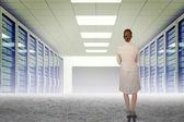 Thinking businesswoman against server hallway — Stock Photo