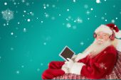 Father christmas listening to music with tablet — Stock Photo