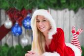 Composite image of festive blonde using tablet pc — Stock Photo