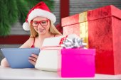 Composite image of festive blonde shopping online with tablet pc — Stock Photo
