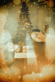 Festive mother and daughter opening a glowing — Stock Photo